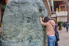 People touch the Big spirit stone in jian an temple shanghai city china royalty free stock images