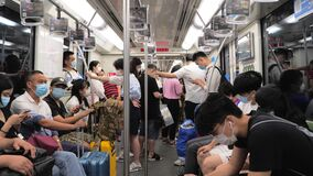 Shanghai, China - July 4, 2020: Passengers ride on the busy subway metro during rush hour, view from inside the