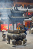 SHANGHAI, CHINA: Large traditional metal structure with beautiful carvings, man making fire inside and smoke coming out Stock Photography