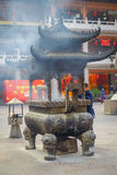SHANGHAI, CHINA: Large traditional metal structure with beautiful carvings, man making fire inside and smoke coming out Stock Photo