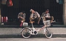 SHANGHAI, CINA: Tre lavoratori rompono il tempo, riposante fotografia stock libera da diritti