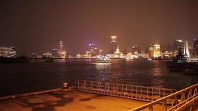 SHANGHAI - 19 MARZO 2018: La vista dell'argine di Pudong alla notte, ha illuminato brillantemente la vela della barca turistica a stock footage