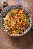 Shanghai nötköttnudlar Udonnudlar med wokar stekte marinerade nötköttremsor i soya med pak choi arkivfoto
