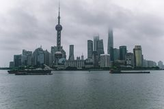 Shanghai skyline on a cloudy day with the skyscrapers covered in clouds and mist royalty free stock image