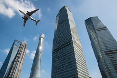 Shanghai skyscrapers buildings and a plane flying overhead at in Stock Photo