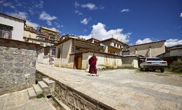 Shangri-La, China - September 25, 2017: Monk walks down the road in Songzanlin Monastery. Shangri-La, China - September 25, 2017: Monk walks down the road in stock image