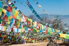 SHANGRILA, CINA - 13 MARZO 2015: Bandiera di preghiera al tempio di Baiji Una chitarra elettrica dello stratocaster del F Fotografia Stock