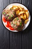 Shank Ossobuco with a garnish of fried potato slices and fresh t. Omatoes close-up on a plate on the table. Vertical top view from above stock images