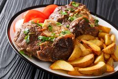 Shank Ossobuco with a garnish of fried potato slices and fresh t. Omatoes close-up on a plate on the table. horizontal royalty free stock image