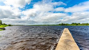 Shannon River with calm waters with a small pier and green vegetation. Wonderful spring day in the county of Westmeath, Ireland royalty free stock image