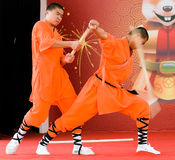 Shaolin Demonstration. Two shaolin performers demonstrating the efficacy of qi by breaking a stout stick over the arm of another, in a public performance as part stock photography