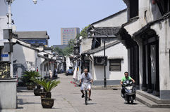 Shaoxing China. A chinese man on a bicycle and moped riding down a street surrounded by chinese architecture within the city of Shaoxing China in zhejiang royalty free stock photography