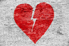 Shape of broken heart. Painted on white brick wall stock image