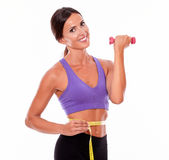 In shape brunette woman lifting weight. In shape woman lifting weight, looking at camera and smiling, while measuring her waist and wearing violet and black Stock Photo