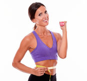 In shape brunette woman lifting weight. In shape woman lifting weight, looking at camera, smiling, while measuring her waist wearing violet and black gymnastic Royalty Free Stock Photography