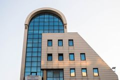 Shape of a building with small windows. A part of a  modern building with small windows,of  offices and  a small cafe,in a greek town thessaloniki Stock Photo