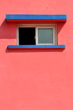 Shape and color of construction element. A small window and shadow on pink color wall, shown as geometric shape and color of the architecture Royalty Free Stock Photo