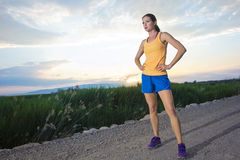 In Shape female Runner at Sunrise. A female runner rests after taking a long morning run. Beautiful sunrise in the background. Lots of copy space Royalty Free Stock Photo