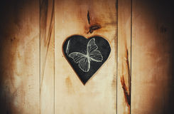 Shape of Heart and Butterfly. Hole in shape of heart in wooden door with drawings of a butterfly royalty free stock images