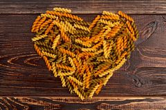 Shape of heart from coloful fusilli pasta. Dried pasta in heart shape on brown wooden background, top view. Love and romance concept Stock Photos