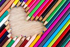 Shape of heart from colorful pens on wooden table Stock Photo