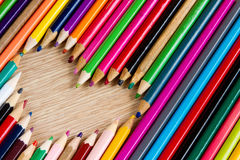 Shape of heart from colorful pens on wooden table Stock Images