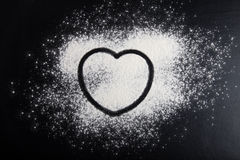 Shape of heart drawn on the flour on a black background Royalty Free Stock Image