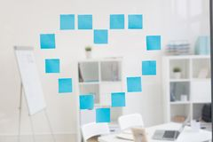 Shape of heart. Heart made up of blue notepapers on transparent board in office Royalty Free Stock Images