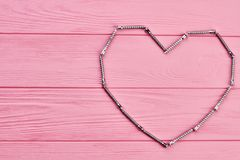 Shape of heart made from hardware. Valentines holiday background with heart shape made from metal fastener, copy space Royalty Free Stock Images