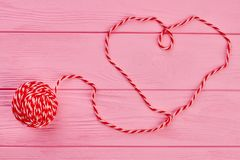 Shape of heart from red woollen thread. Ball of yarn on pink wooden background. Valentines Day concept Stock Image