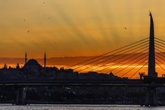 Istanbul on sunset. Shape of Istanbul city in the sunset light from a bosphorus bridge with a lot of sunrays and gulls in the sky stock photo