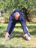 In shape old man stretching outdoor royalty free stock photo