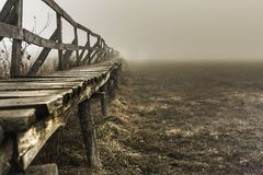 Shape of a pier near a lake, wintertime on a foggy morning, in S stock photography