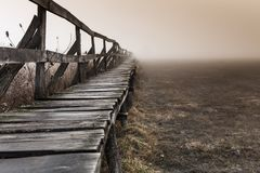 Shape of a pier near a lake, wintertime on a foggy morning, in Sic illage, nsylnia, Romania stock photo