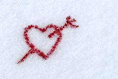 The shape of a red heart pierced by an arrow in the snow in wint. Er, February 14 - Valentine`s Day Stock Photo