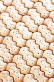 Shaped browned crisp biscuits as tile background Royalty Free Stock Image