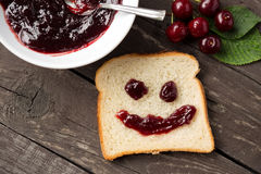 Shaped happy face bread with cherry jam Stock Photos