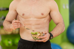 Shaped and healthy body building man holding a fresh salad bowl,shaped abdominal.  Stock Photography