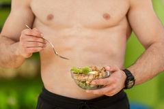 Shaped and healthy body building man holding a fresh salad bowl,shaped abdominal.  Royalty Free Stock Photos