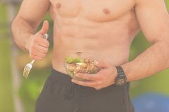 Shaped and healthy body building man holding a fresh salad bowl,shaped abdominal.  Royalty Free Stock Images