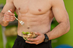 Shaped and healthy body building man holding a fresh salad bowl,shaped abdominal.  Stock Photo