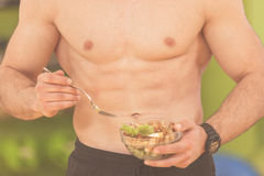 Shaped and healthy body building man holding a fresh salad bowl,shaped abdominal.  Royalty Free Stock Photography
