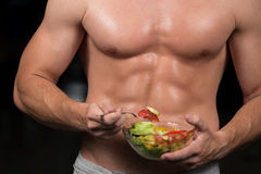 Shaped and healthy body building man holding a fresh salad bowl,shaped abdominal. Shaped and healthy body building man holding a fresh salad bowl, shaped Stock Photography