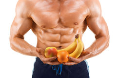 Shaped and healthy body man holding a fresh fruits, shaped abdominal, isolated on white Royalty Free Stock Photos
