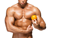 Shaped and healthy body man holding a fresh orange Royalty Free Stock Photos