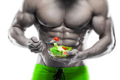 Shaped and healthy body man holding a fresh salad bowl Royalty Free Stock Images