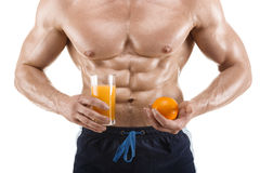 Shaped and healthy body man holding a glass with juice and orange, shaped abdominal, isolated on white Royalty Free Stock Photos