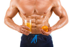 Shaped and healthy body man holding a juice and orange, shaped abdominal, isolated on white. Background Royalty Free Stock Photo