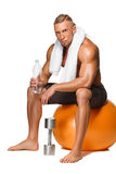 Shaped and healthy body man sitting on fitness Royalty Free Stock Photos