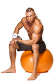 Shaped and healthy body man sitting on fitness Royalty Free Stock Image